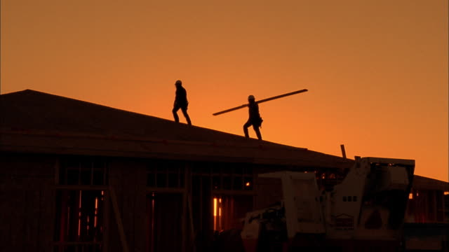Medium shot silhouette of two construction workers carrying plank on roof /  Phoenix, Arizona