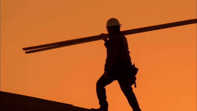 Medium shot silhouette of two construction workers carrying planks on roof /  Phoenix, Arizona