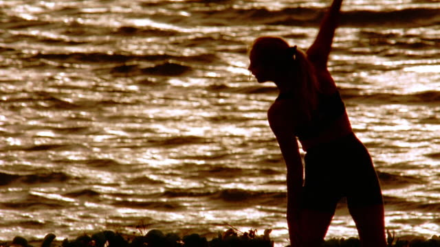 Medium shot silhouette of woman performing stretching exercises with water in background / Maui, Hawaii