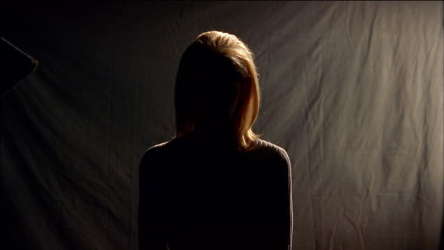 medium shot silhouetted blonde woman - freisteller neutraler hintergrund stock-videos und b-roll-filmmaterial
