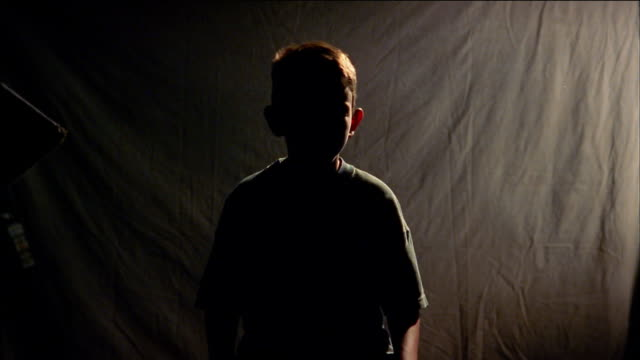 Medium shot silhouetted boy turning head