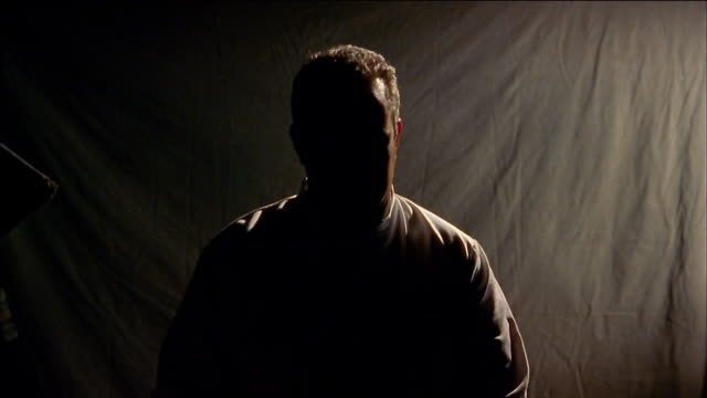 stockvideo's en b-roll-footage met medium shot silhouetted man turning head - back lit