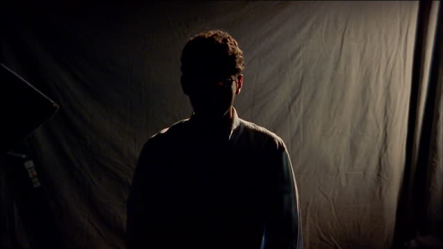 stockvideo's en b-roll-footage met medium shot silhouetted man with eyeglasses and curly hair - back lit