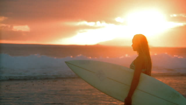 stockvideo's en b-roll-footage met medium shot silhouetted woman holding surfboard on beach at sunset / tahiti - driekwartlengte
