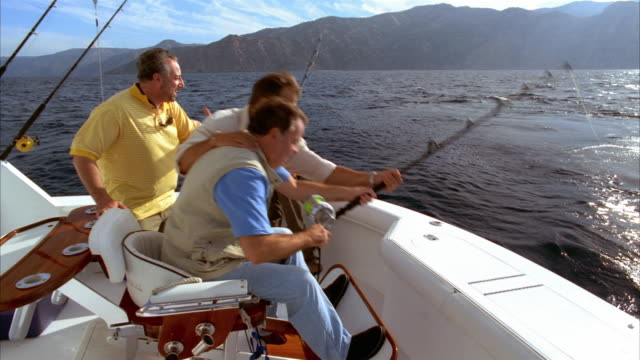 medium shot sitting in fighting chair on yacht and struggling with fish on his line as his friends surround him/ man scooping up red snapper in net/ california - fishing rod stock videos and b-roll footage