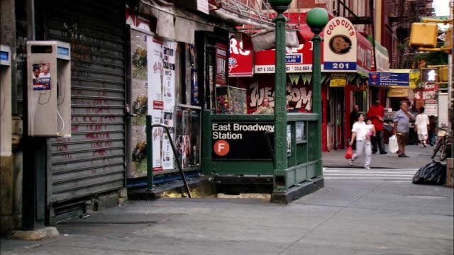 medium shot skateboarders exiting east broadway subway station and skating away / lower east side, nyc - 階段点の映像素材/bロール