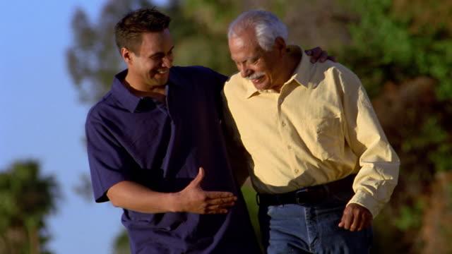 medium shot slow motion senior man and younger man walking + talking outdoors / arizona - sohn stock-videos und b-roll-filmmaterial