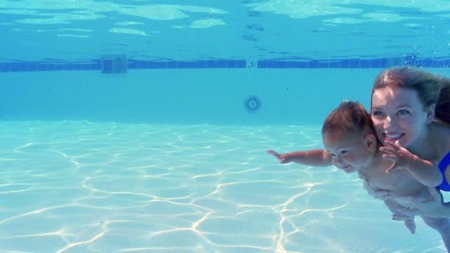Medium shot slow motion woman swimming with baby underwater