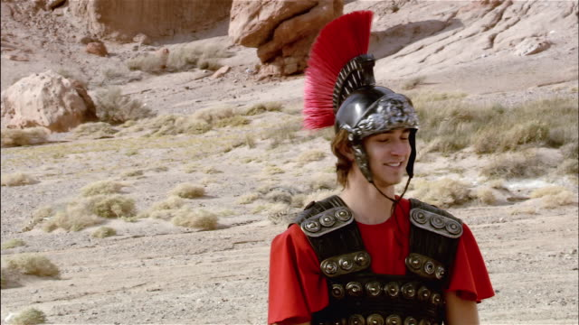 medium shot smiling actor wearing a roman soldier costume / slate appearing in foreground / actor putting on serious face / red rock canyon state park, california - roman soldier stock videos and b-roll footage