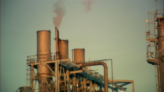 Medium shot smokestack at top of oil refinery at dusk/ Los Angeles, California
