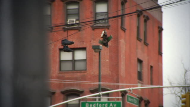 vídeos y material grabado en eventos de stock de medium shot sneakers hanging from telephones wires on bedford avenue / williamsburg, brooklyn, new york, usa - línea telefónica
