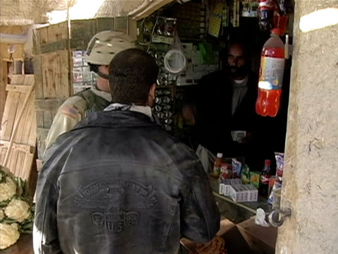 medium shot soldier and man in leather jacket at shop/ shop owner stepping out carrying money/ afghanistan - operazione enduring freedom video stock e b–roll