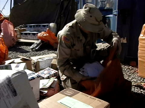 medium shot soldier crouching and sorting mail on us military base/ afghanistan - operazione enduring freedom video stock e b–roll