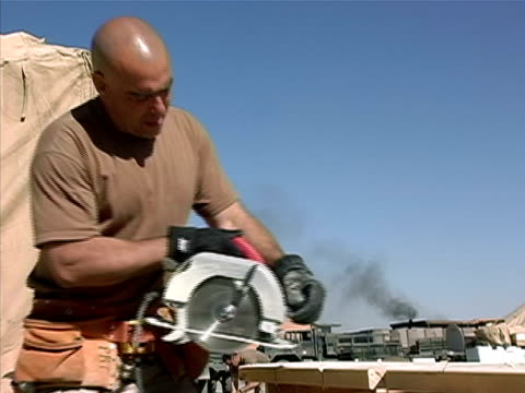 medium shot soldier cutting wood with circular saw on military base/ afghanistan - operazione enduring freedom video stock e b–roll
