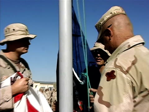 medium shot soldiers raising virginia flag on us military base/ tilt up flag rising/ afghanistan - operazione enduring freedom video stock e b–roll