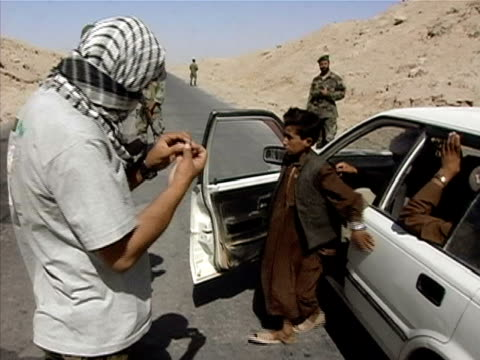 Medium shot soldiers search people in car at checkpoint/ Afghanistan
