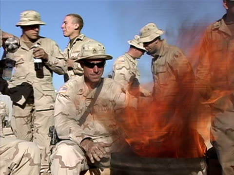 medium shot soldiers sitting by fire outside warming hands and drinking bottled beverage/ afghanistan - ドラム容器点の映像素材/bロール