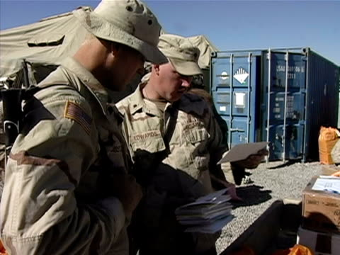 medium shot soldiers sorting mail on us military base/ zoom in hand holding mail/ afghanistan - operazione enduring freedom video stock e b–roll