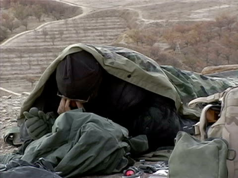 Medium shot solider waking up on ground in sleeping bag/ Afghanistan