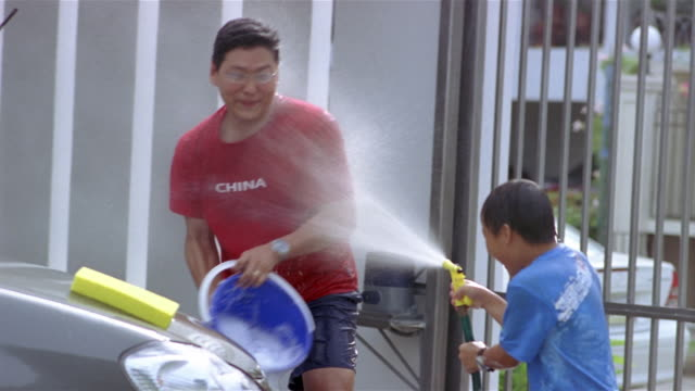 Medium shot son spraying father with hose while washing car / father splashing son with bucket of water