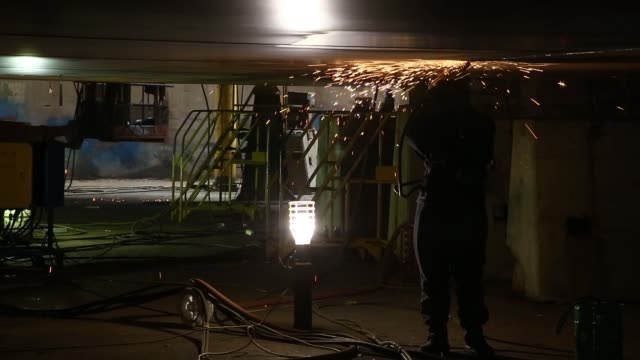 medium shot sparks fly as an employee uses an angle grinder on a ship under construction close up shot sparks fly as an employee uses an angle... - skeppsbyggare bildbanksvideor och videomaterial från bakom kulisserna