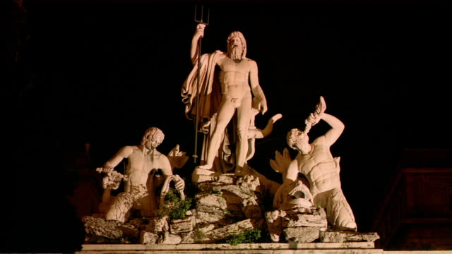 Medium shot statue of Neptune between two tritons in fountain in Piazza del Popolo / Rome, Italy
