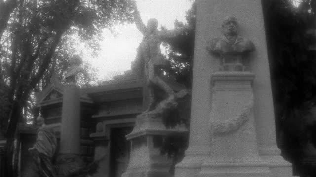 vidéos et rushes de medium shot statues at pere lachaise / pan walkway lined with graves / paris - image en noir et blanc