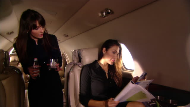 Medium shot Stewardess serving bottled water to businesswoman on private jet/ Miami, Florida, USA