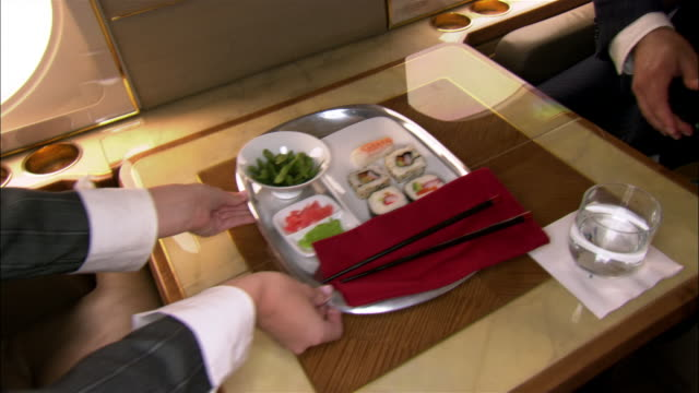 medium shot stewardess serving tray of sushi to businessman in private airplane - 盆点の映像素材/bロール