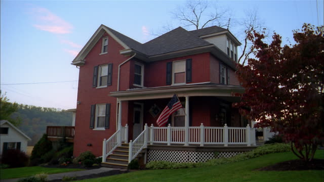 medium shot stone house w/american flag on white painted porch / lights turning on and off - 2003 stock videos & royalty-free footage