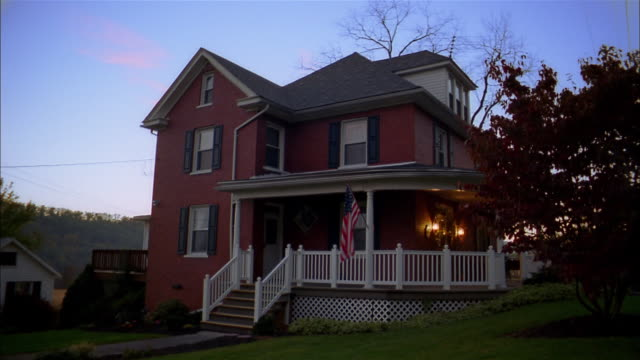 medium shot stone house w/american flag on white painted porch / lights turning on and off - veranda stock videos & royalty-free footage