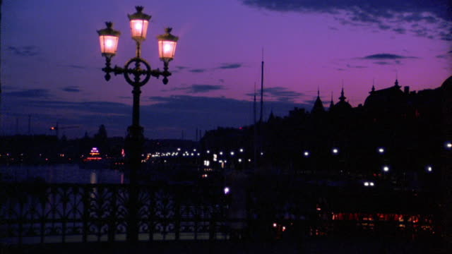 medium shot street light on bridge with traffic and silhouetted buildings in background at twilight / stockholm, sweden - 1993 stock videos & royalty-free footage