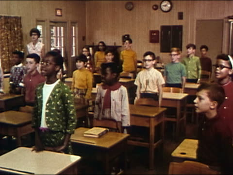 stockvideo's en b-roll-footage met 1968 medium shot students standing behind desks and singing 'america (my country 'tis of thee) / audio - medium filmcompositietype