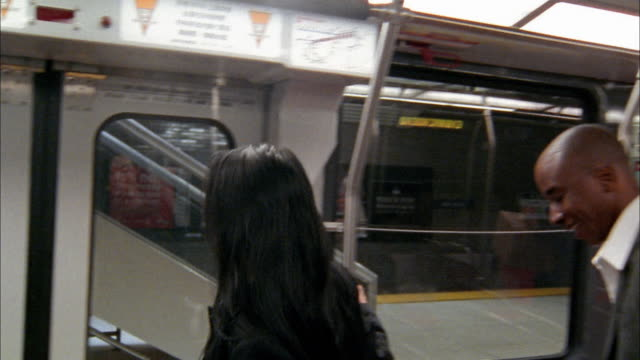 Medium shot subway pulling into station / commuters exiting / pan rumpled commuter carrying large plant