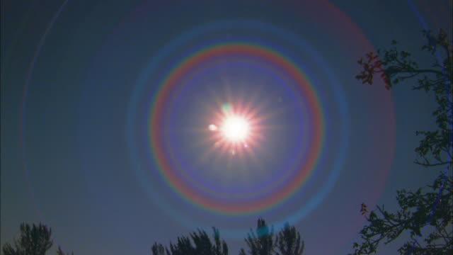 medium shot sun flaring against blue sky - circle stock videos & royalty-free footage
