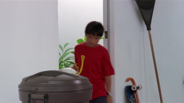 vídeos de stock e filmes b-roll de medium shot surly young boy putting trash bag in garbage can - remover