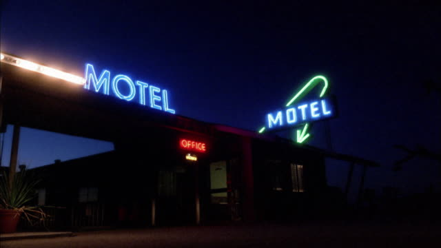 medium shot suv driving into motel entrance at night w/neon signs - schild stock-videos und b-roll-filmmaterial