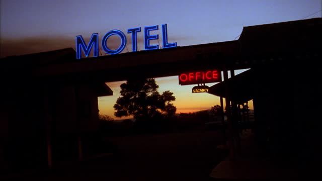 Medium shot SUV driving into motel parking lot at night