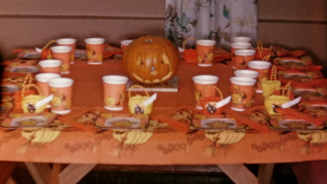 1958 medium shot table set for halloween party with jack o' lantern in center - napkin stock videos and b-roll footage