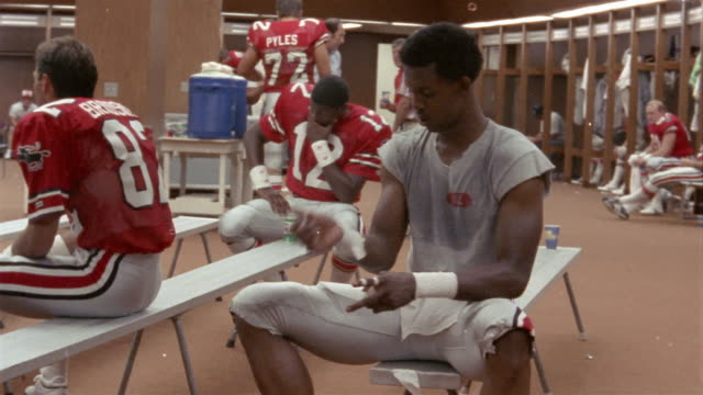 1985 medium shot tampa bay bandits football player wrapping wrists with sports tape in locker room before game / tampa, florida, usa  - locker stock videos and b-roll footage