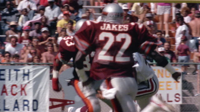 1985 Medium shot Tampa Bay Bandits player running with football and falling during game against Jacksonville Bulls / Jacksonville, Florida, USA