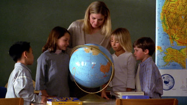 vídeos y material grabado en eventos de stock de medium shot teacher and students examine globe in at teacher's desk in classroom with chalkboard in background - globo terráqueo para escritorio