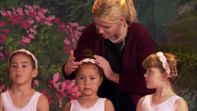 medium shot teacher fixing hair and headbands of girls dressed in tutus - 6 7 jahre stock-videos und b-roll-filmmaterial