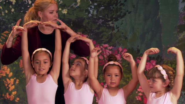 medium shot teacher positioning girls' arms during ballet recital / girls dancing offstage - pacific islander teacher stock videos & royalty-free footage