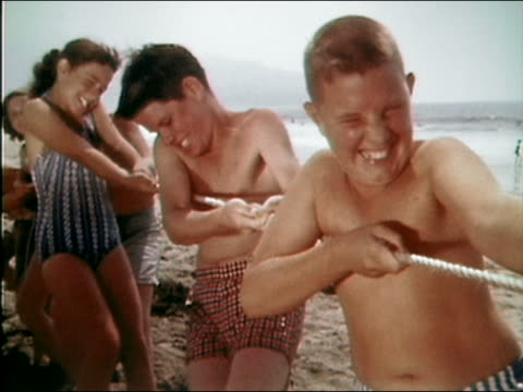 vidéos et rushes de 1961 medium shot team of boys and girls pulling rope during game of tug of war on beach - grimace de pitre