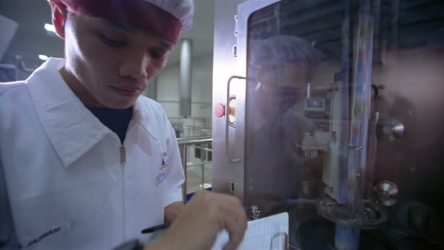 vidéos et rushes de medium shot technician inspecting aseptic packaging chamber at ultra jaya milk processing plant / indonesia - contrôle qualité