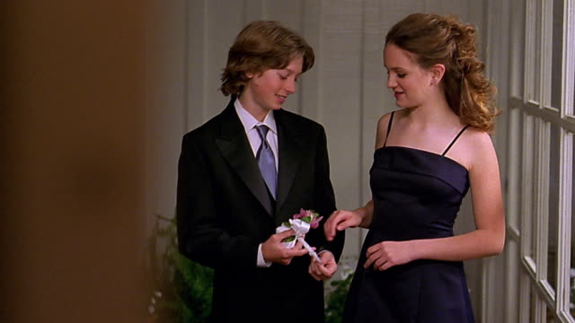 Medium shot teenage boy and girl posing / boy placing corsage on her wrist / leaving