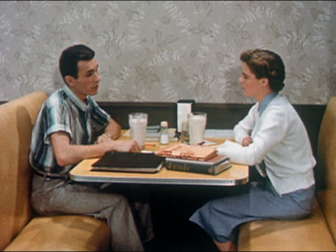1956 medium shot teenage boy and girl sitting at diner booth + talking / shaking hands