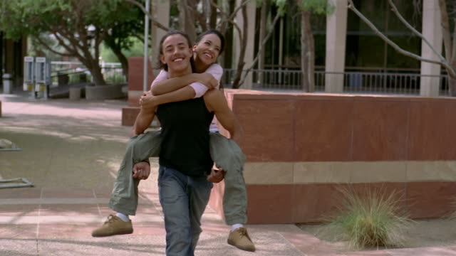 vidéos et rushes de medium shot teenage boy carrying teen girl on his back - couple d'adolescents