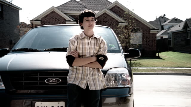 medium shot teenage boy leaning on minivan in driveway of suburban home - 14歳から15歳点の映像素材/bロール